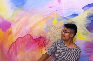 Photo of Katia wearing a black and white striped shirt, glasses and short dark hair in front of a pink, yellow and blue abstract painting.