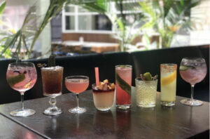 Eight colorful cocktails in varying glasses lined up on a dark table with plants in the background.