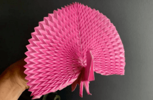 Photo of a pink origami Peacock. The Peacock is being held my a barely visible hand. The background is grey.