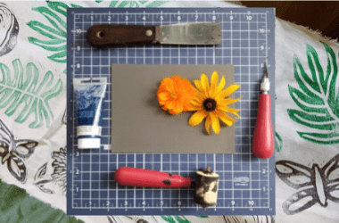 Photo of printmaking Supplies including linoleum, roller, carving tools and paint. There are also two flowers in the photo, one yellow and one orange. There is a background image of green leaf prints.
