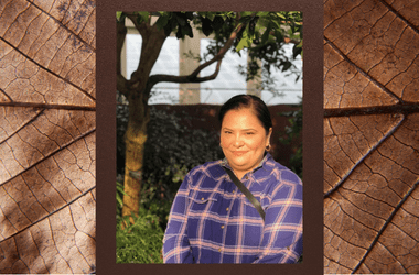 Portrait of Lorena Lopez. She is in front of a tree and window. Lorena has brown hair and eyes and is wearing a purple plaid shirt.